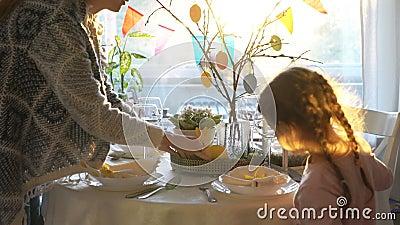 妇女和她的小女儿布置与兔宝宝的复活节欢乐桌并且怂恿装饰 影视素材