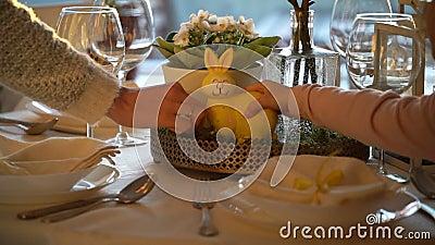 妇女和她的小女儿布置与兔宝宝的复活节欢乐桌并且怂恿装饰 股票录像