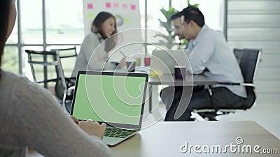 妇女在办公室递有绿色屏幕的键入的便携式计算机在桌上 特写镜头