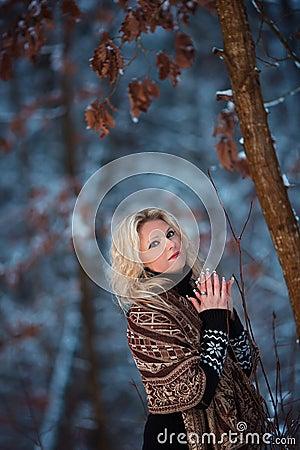 妇女在雪冬天森林里