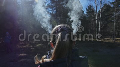 妇女有从她的头和耳朵出来的抽烟 在女孩后是户外仪式的礼节罐烟灰缸 股票录像