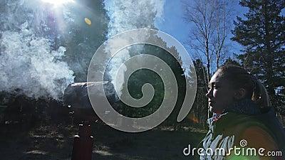 妇女有从她的头和耳朵出来的抽烟 在女孩后是户外仪式的礼节罐烟灰缸 股票视频