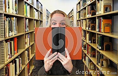 妇女阅读书在图书馆里