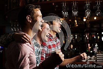 三个年轻人的夜场人生_酒吧观看的比赛和呼喊的三个年轻人.