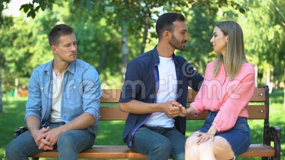 孤独的男人坐在公园的长椅上,看着情侣的浪漫情感 股票视频