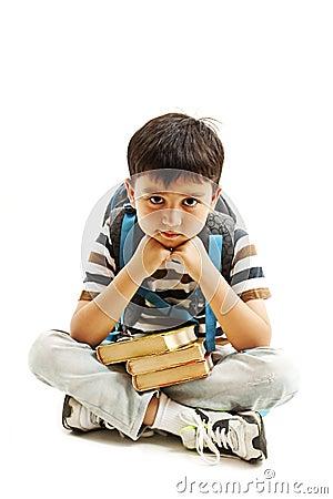 学习感到厌烦,挫败和淹没的男小学生家庭作业 小男孩下来坐在白色背景图片