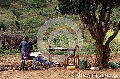 学习的十几岁的男孩户外,莫桑比克 编辑类库存图片