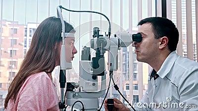 室内眼科治疗 — 一位医生用一台特殊机器检查年轻女性的视力 — 一个宽敞的空间 影视素材