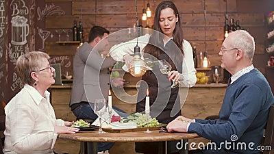 对一对老夫妇的女服务员倾吐的酒在日期 股票录像