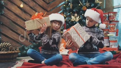 小双胞胎坐在圣诞树下,摇摇晃晃地摆弄着礼物盒,找出里面的东西 股票视频
