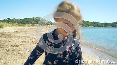 小女孩沿一个离开的北海滩跑在一个晴朗的夏日 股票录像