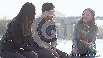 小组三个愉快的亚裔少年坐街道在日落时间 影视素材