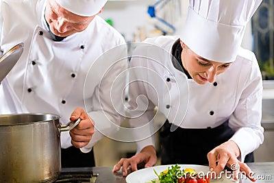 小组的二位主厨在旅馆或餐馆厨房里