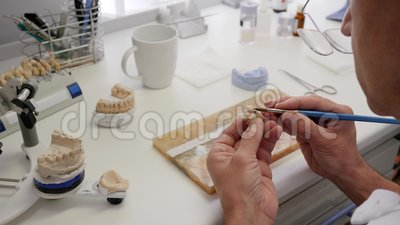 工作的牙科技师在植入管生产实验室画在假牙的白色油漆 影视素材