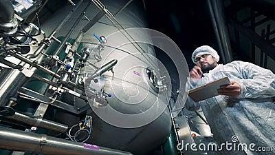 巨型的蒸馏的水库和一位男性专家观察它运作的过程 股票录像