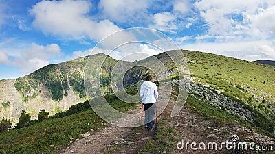 带着徒步杖的女人在山里行走 史诗山景 股票录像