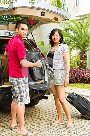 带着手提箱的亚洲夫妇装箱汽车为节假日