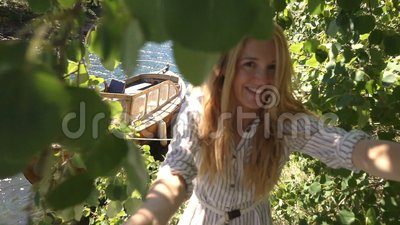 带领她的往村庄和小船的少妇人在岸 影视素材