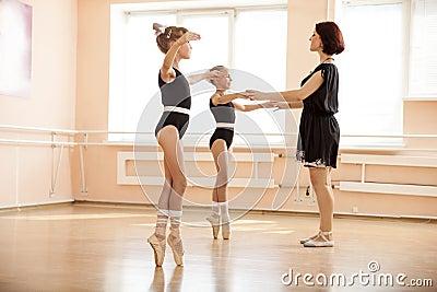 帮助女孩的老师跳舞en pointe在芭蕾类.图片