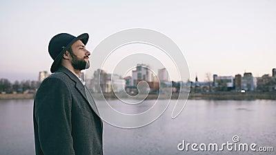 帽子和外套观看的都市风景和作白日梦的年轻有胡子的旅游人,当站立在河沿时 影视素材