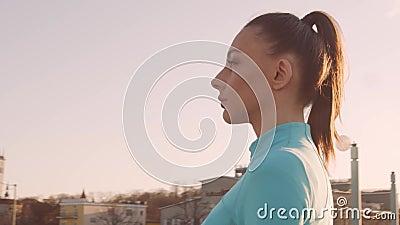 年轻、漂亮、体态活泼的女人,在户外进行晚间训练 城市日落背景 股票录像