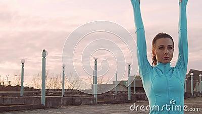 年轻、漂亮、体态活泼的女人,在户外进行晚间训练 城市日落背景 股票视频