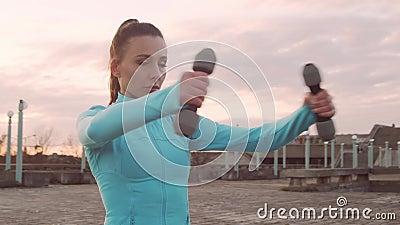 年轻、漂亮、运动型的女子,在户外接受哑铃式夜间训练 城市日落背景 股票录像