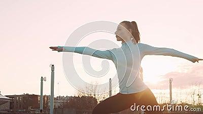 年轻、漂亮、运动型的女性,在户外进行晚间瑜伽训练 城市日落背景 股票视频
