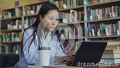 年轻亚裔学生女孩在与堆的桌上书在运作的大学图书馆里坐便携式计算机,喝 股票录像