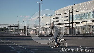 年轻人骑沿街道的一辆自行车 股票录像