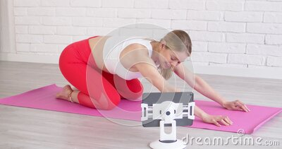 年轻体育女,在家练瑜伽的平板电脑 她在网上看课或教程 股票录像