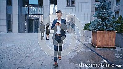 年轻商人使用智能手机,当走在大城市商业区街道上时 古典地穿戴 ?? 股票视频