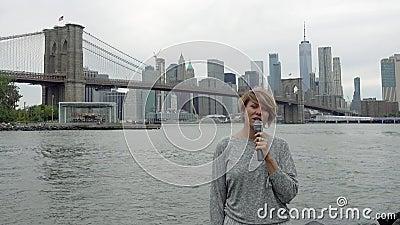年轻女人电视记者在曼哈顿摩天大楼背景播放  股票视频