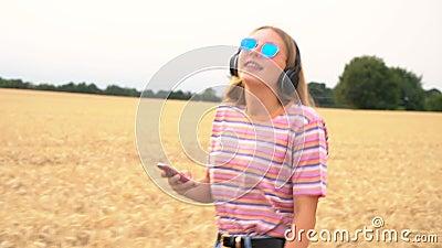 年轻女孩戴着蓝色太阳镜在田野里听手机和无线耳机播放音乐 股票视频