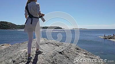 年轻女性摄影师攀登在海上的峭壁拍照片 股票视频