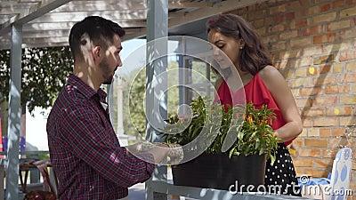 年轻微笑的有胡子的农夫谈论花与在老房子前面的有吸引力的年轻女人身分 ??  影视素材