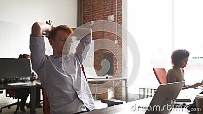年轻男性雇员结束计算机工作感觉满意对结果 影视素材