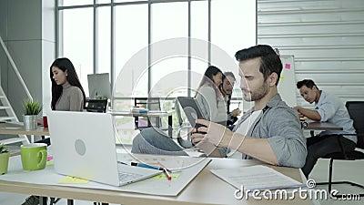 年轻白种人运作创造性的项目的聪明的便衣的人现代同事,当花费时间在办公室时