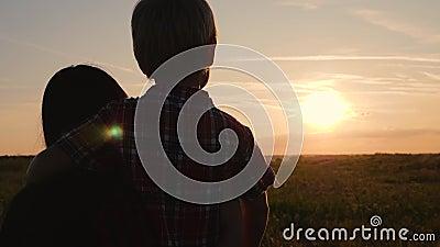 幸福的家庭 母子看着夕阳 在户外旅行和散步 幸福与健康的概念 股票录像