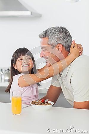 微笑的小女孩拥抱她的父亲在厨房里.图片