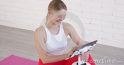 微笑的年轻人坐在瑜伽垫上浏览平板电脑 在线学习概念 股票视频