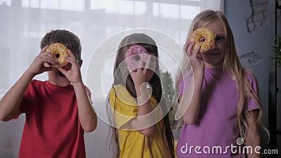 快乐的童年,无忧无虑的孩子们在联合庆祝时用双眼看着甜甜圈 股票录像