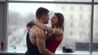 恋人表现出爱 男性爱好健美者举行一起打旋他的妇女,亲吻和拥抱 影视素材
