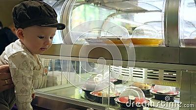 惊奇的婴孩在用不同的寿司的陈列室看在军用餐具的移动的板材 股票视频