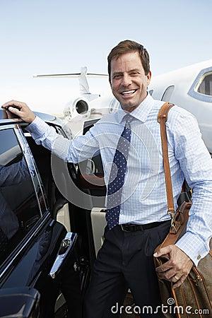愉快的商人乘在机场的汽车