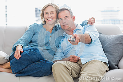 愉快的夫妇拥抱和坐看电视的长沙发
