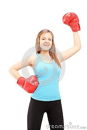 愉快的女运动员佩带的拳击手套和打手势胜利