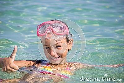 愉快的小女孩游泳与潜水的一个面具.