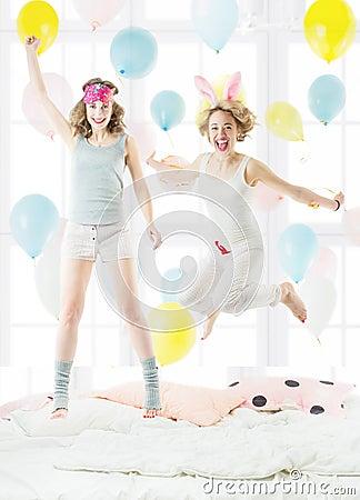 跳跃在睡衣裤的床上的两个美丽的年轻朋友 睡衣派对 快乐的愉快的图片