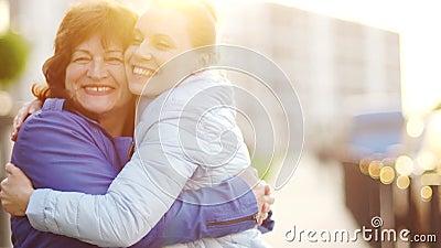 愉快的母亲和她的aduit女儿 妇女轻轻地拥抱和快乐看照相机 家庭传统 母亲 股票录像